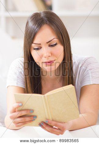 Girl reading book in domestic room