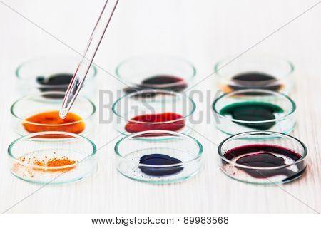 Various colored chemicals in petry dish and pippete to dissolve
