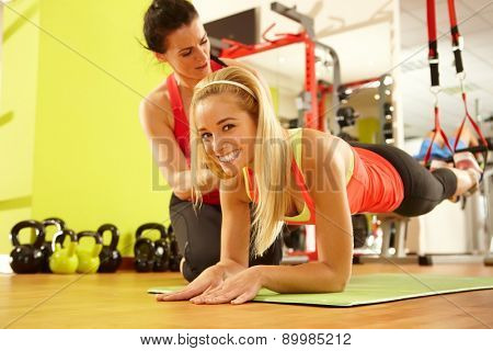 Happy sporty woman training in gym with coach.