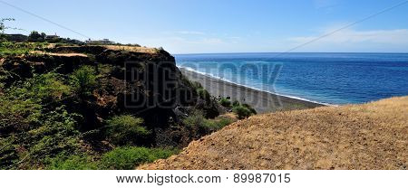 Dry River Bank Empties Into A Black Sand Beach