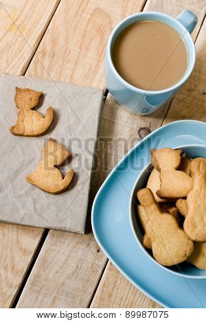 Sweet Tasty Cookies In The Blue Plate, A Cup Of Coffee With Milk And Notebook On Wooden Unpainted Ba