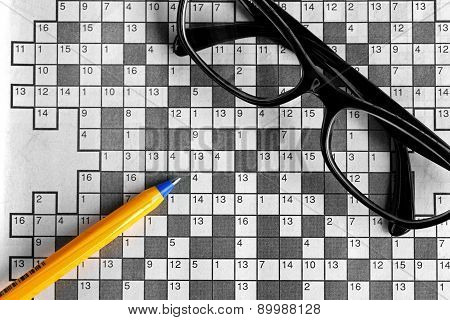 Top View Of Blank Crossword Puzzle With Black Eyeglasses And A Pen