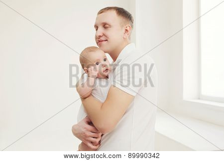 Happy Father Hugging His Baby At Home In White Room