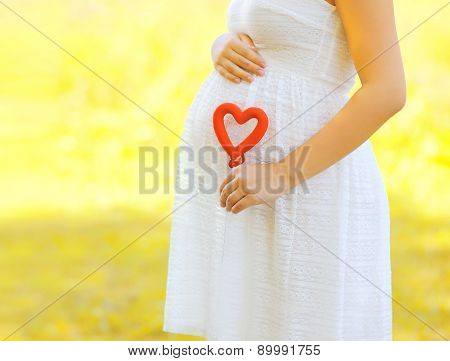 Pregnancy, Maternity And New Family Concept - Pregnant Woman Holding Red Heart Symbol Outdoors In Su
