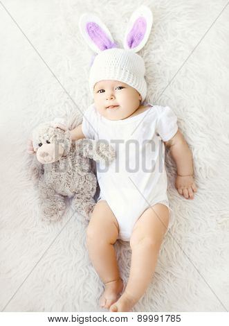 Soft Photo Of Sweet Baby In Knitted Hat With A Rabbit Ears And Teddy Bear Lying On The Bed, Top View