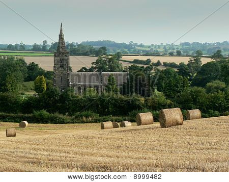Harvest field with rolls of hay and a church in background