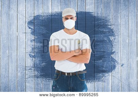 Man with paintbrush standing arms crossed by ladder against wooden planks