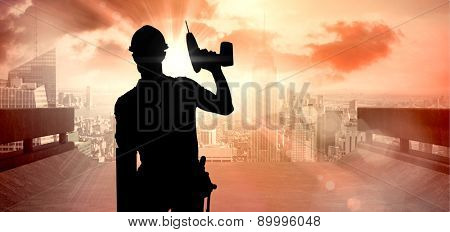 Carpenter showing thumbs up while holding drill machine against sun shining over road and city