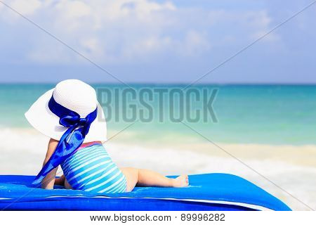 little girl in big hat on summer beach