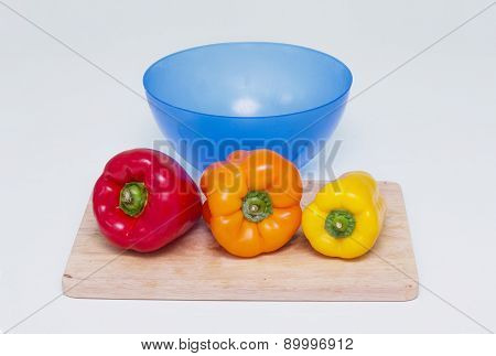 Three whole peppers of different colors on the board for cutting and blue bowl for food