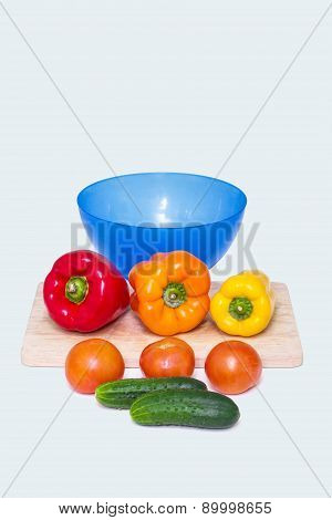 Different whole vegetables of different colors next to a bowl for a salad