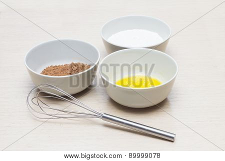 Bowl with home eggs, bowl with cocoa and bowl with milk, mixer