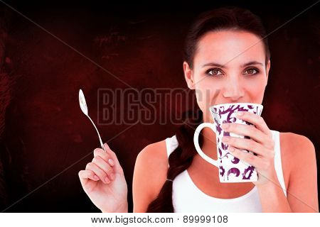 Pretty brunette having cup of tea against dark background
