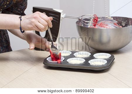 Hand filling cupcakes molds with dough