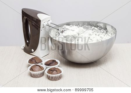 Mixer near cupcakes and a bowl with butter cream