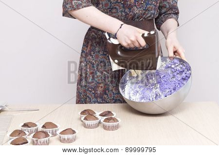 Woman with kitchen mixer whisking cream for cupcakes