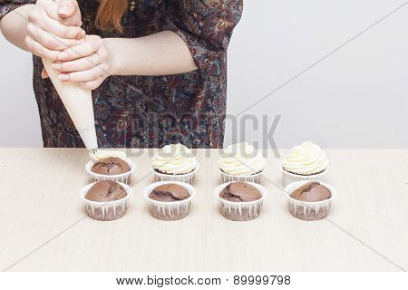 Woman decorates a cupcake with cream