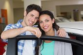 image of showrooms  - Smiling couple holding their new car key at new car showroom - JPG
