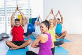 pic of senior class  - Portrait of female instructor with class practicing yoga in fitness studio - JPG