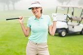 stock photo of buggy  - Happy golfer with golf buggy behind on a foggy day at the golf course - JPG