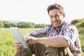 picture of tablet  - Young man using tablet in the countryside on a sunny day - JPG