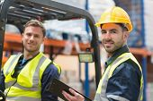 pic of forklift  - Smiling warehouse worker and forklift driver in warehouse - JPG