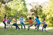 picture of tug-of-war  - Children having a tug of war in park on a sunny day - JPG