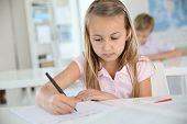 stock photo of schoolgirl  - Cute schoolgirl writing on notebook - JPG