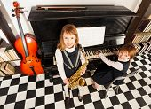 picture of saxophones  - View from top of girls in school uniform dresses playing on the alto saxophone and the piano indoors with black and white checked floor - JPG