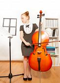 picture of musical instrument string  - Beautiful girl holding the string to play violoncello looking at musical notes in musical school - JPG