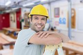 picture of step-ladder  - Happy technician leaning on step ladder against workshop - JPG