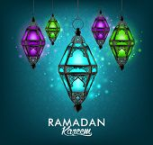 stock photo of kareem  - Beautiful Elegant Ramadan Kareem Lantern or Fanous Hanging With Colorful Lights in Night Background With Islamic or Arabic Pattern - JPG