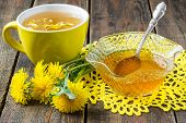 foto of dandelion  - Spring jam of dandelions flower tea in a yellow cup and a flowers dandelion on a yellow knitted napkin - JPG