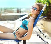 stock photo of sunbather  - Portrait of beautiful woman in swimsuit sunbathing on the beach - JPG