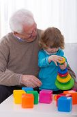 image of grandpa  - Smiling grandpa and grandchild building color tower - JPG
