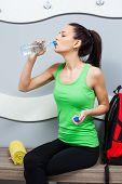 stock photo of training room  - Girl drinking water in locker room before fitness training - JPG