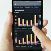 picture of statements  - Smart phone showing financial income statement on stock market - JPG
