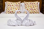 stock photo of ero  - Two swans heart shaped made from towels on honeymoon bed - JPG