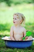 stock photo of wash-basin  - little girl sits in basin with water - JPG