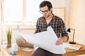 foto of concentration man  - Concentrated young man looking through blueprint while leaning at his working place - JPG
