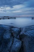 image of jetties  - Long exposure of Swedish archipelago coastal landscape with cliffs and jetty - JPG