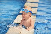 image of goggles  - Happy smiling baby with underwater goggles is having fun playing with splashes in blue water in pool before swimming lessons - JPG