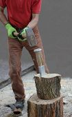 picture of firewood  - woodworking man with a splitting wedge preparing firewood - JPG