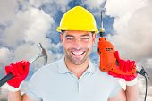 picture of hammer drill  - Happy repairman holding hammer and drill machine against blue sky with white clouds - JPG