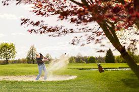 stock photo of golf bag  - Senior golf player hitting ball from sand bunker - JPG