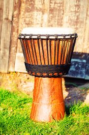 image of congas  - Original african djembe drum with leather lamina on green in sun light - JPG