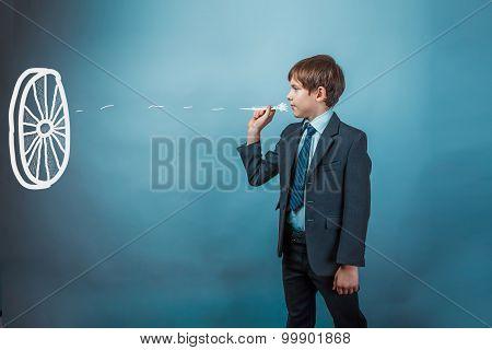 Teen boy businessman throwing darts at a target dart on a blue b