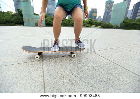 young woman skateboarder riding skateboard on city