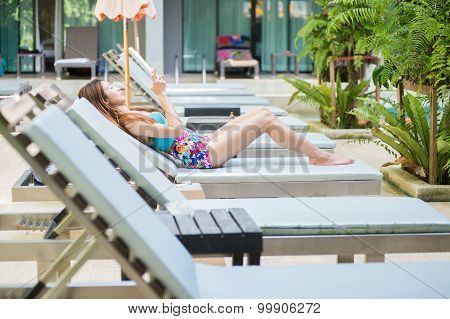 Beautiful Woman Using A Smart Phone On Lounger Near Swimming Pool In Hotel, Krabi, Thailand