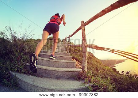 fitness woman runner trail running on seaside mountain stairs training for cross country running.